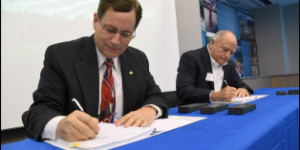 "Philip W. Allin, Fairfax Water's Chairman, and William ""Kim"" Duke, Vulcan's Mideast Division President, sign the final documents for the official sale and purchase of a portion of Vulcan Materials land for the creation of a new reservoir in Lorton, Virginia, Oct. 25. (Photo courtesy of Fairfax Water)"